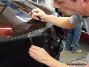 Professional Clear Bra Installation in Aspen-Basalt Area technician cuts off unneeded clear bra film