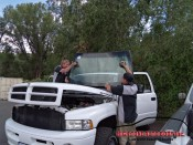 technicians placing the prepped windshield onto the pickup truck